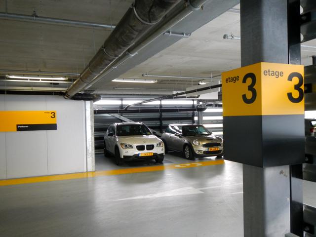 Parkeerverdiepingen met kleurcodering op vloer en signs.